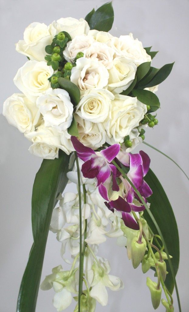 cascading bouquet made with roses, orchids, hypericum berries and greenery