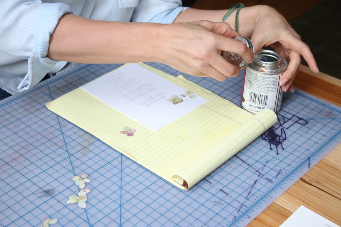 Glue pressed flowers to your wedding invitations with rubber cement