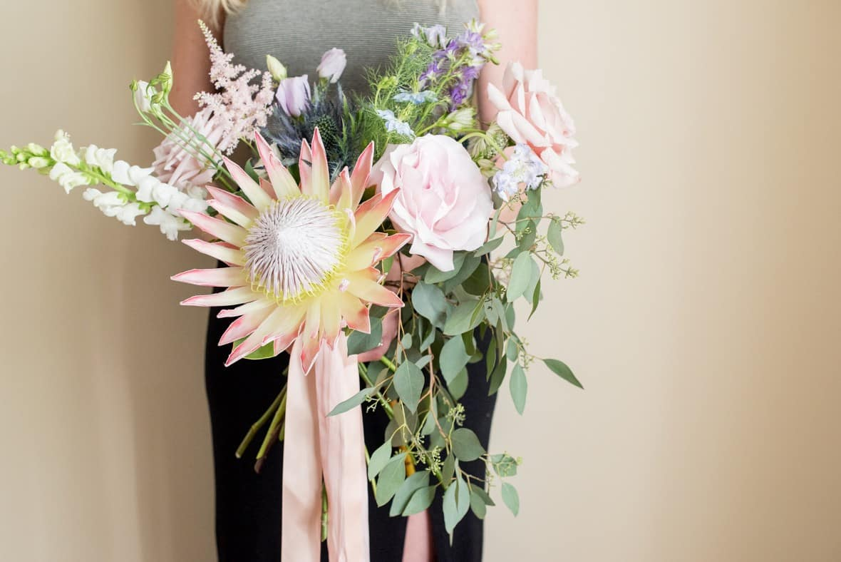 Peony and garden rose bouquet, whimsical designs with horizontally focused greenery with short ribbons